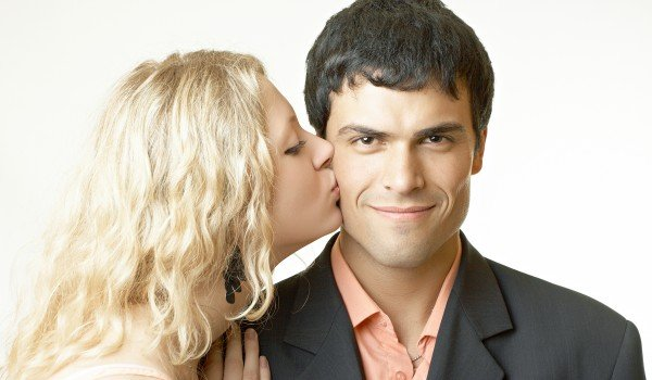 Фото: Девушка целует парня в щеку