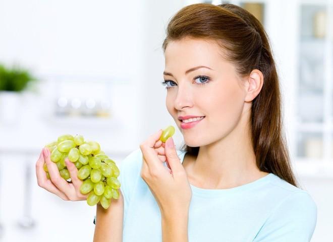 девушка кушает виноград